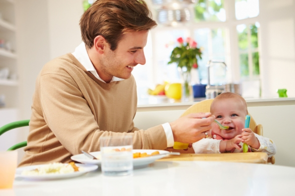Father Feeding Baby Sitting In High Chair At Mealtime